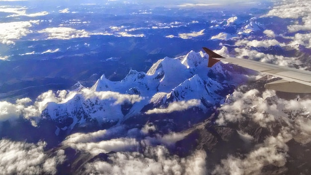 Vliegtuigmening van rotsachtige bergen die overdag in de sneeuw onder het zonlicht worden behandeld Gratis Foto