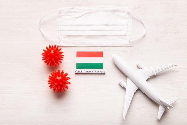 Vliegtuigmodel en gezichtsmasker en vlag hongarije. coronapandemie. vluchtverbod en gesloten grenzen voor toeristen en reizigers met coronavirus covid-19 uit europa en azië. Premium Foto