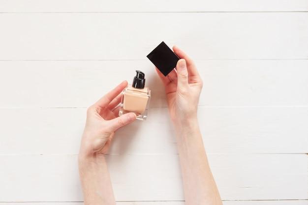Vloeibare foundation met make-up product in handen van de vrouw. Premium Foto