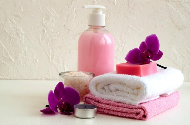Vloeibare zeep en twee handdoeken op een witte achtergrond. Premium Foto