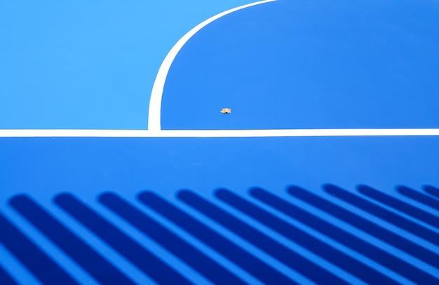 Vloerachtergrond van een intens blauw sportveld met witte lijnen. Premium Foto