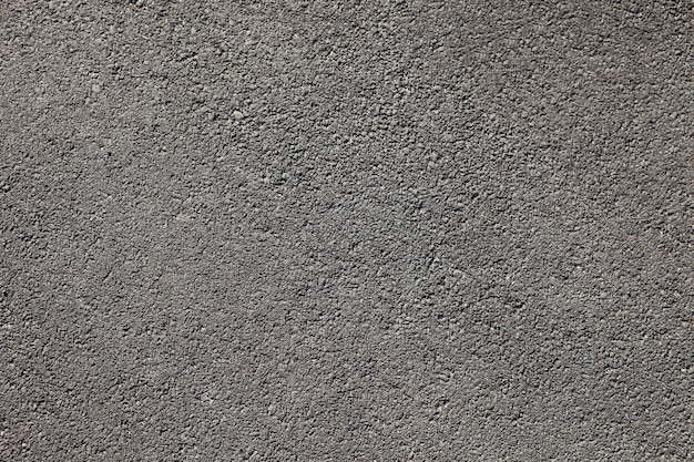 Vlotte donkergrijze de textuurachtergrond van de asfaltbestrating met kleine rotsen Premium Foto