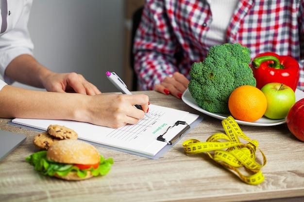 Voedingsdeskundige stelt een dieetplan op voor een vrouw met overgewicht Premium Foto