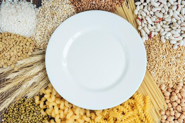 Voedingsmiddelen rijk aan koolhydraten op houten achtergrond. brood, pasta, parelgort en haver. Premium Foto