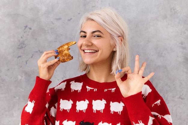 Voedsel, bakkerij en gebak. schattige tienermeisje houdt van chocoladecroissant die een strikt dieet volgt, zichzelf helpt met een zoet dessert zonder wroeging, niet bang om extra gewicht te krijgen, ok gebaar toont Gratis Foto