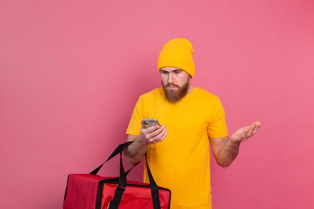 Voedsel bezorgen verontwaardigd ontevreden kijken naar de telefoon op roze Gratis Foto