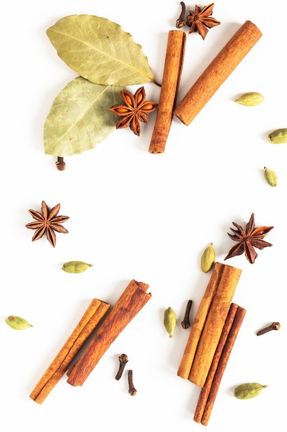 Voedsel concept mix van biologische kruiden steranijs, kaneel, bay en kardemom peulen op wit Premium Foto
