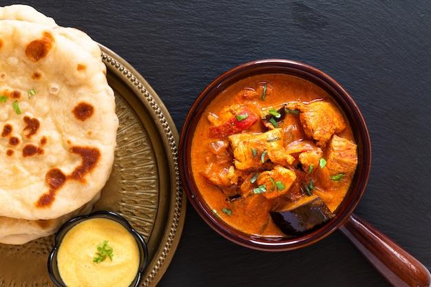 Voedsel concept zelfgemaakte tandoori chicken masala curry met naan brood en yoghurt onderdompelende saus Premium Foto