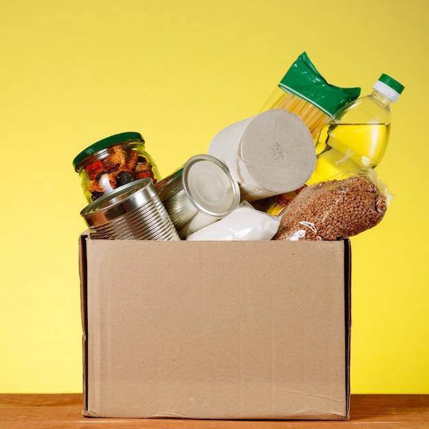 Voedsel donatie concept. donatiebox met voedsel voor donatie op gele backround. bijstand aan ouderen in de context van de coronaviruspandemie. vierkant beeld Premium Foto