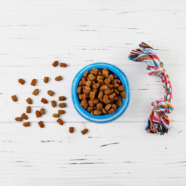 Voedsel en speelgoed voor honden op witte houten oppervlak Gratis Foto