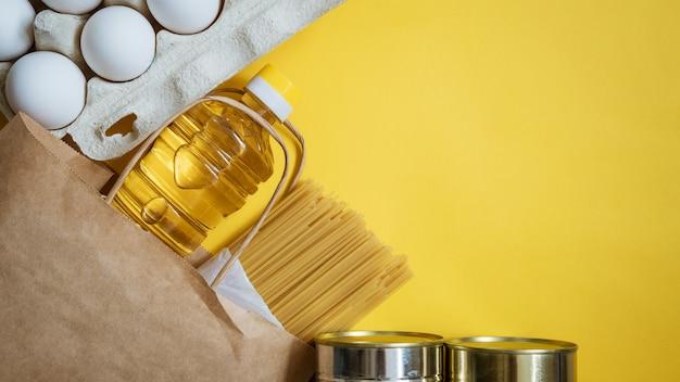 Voedsel in een kartonnen doos op een gele achtergrond Gratis Foto