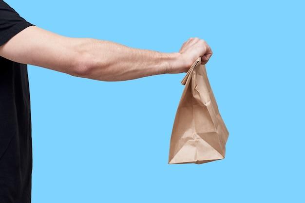 Voedsel levering concept. koerier in zwarte uniforme papieren zak met afhaalmaaltijden op blauwe achtergrond Premium Foto