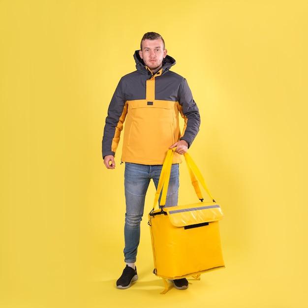 Voedsel levering lachende blanke jonge man in geel jasje en met thermoszak op zijn schouders op geel Premium Foto