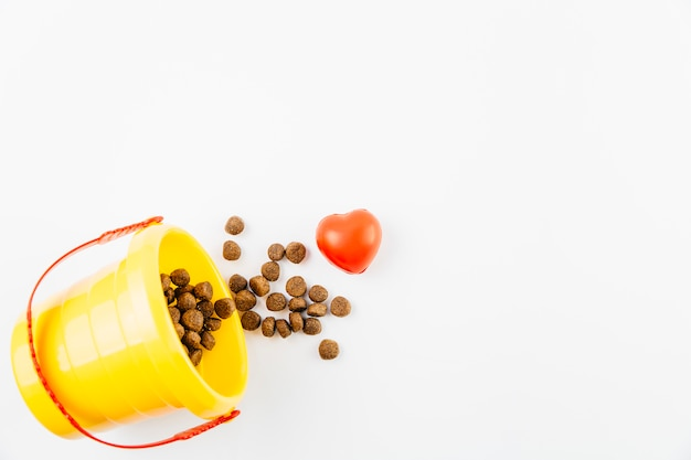 Voedsel voor huisdieren in emmer op witte oppervlakte Gratis Foto