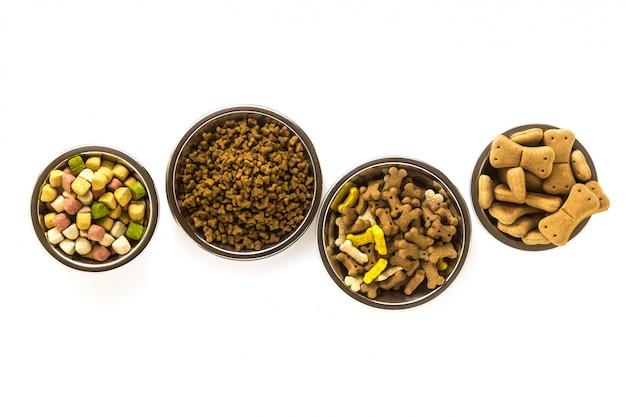 Voedsel voor huisdieren in kommen en speelgoed dat op witte achtergrond wordt geïsoleerd Premium Foto