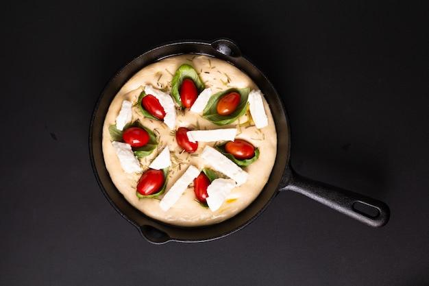 Voedselconcept het toenemen deeg voor eigengemaakte organische focaccia in pan van de koekepanijzer op zwarte achtergrond met exemplaarruimte Premium Foto