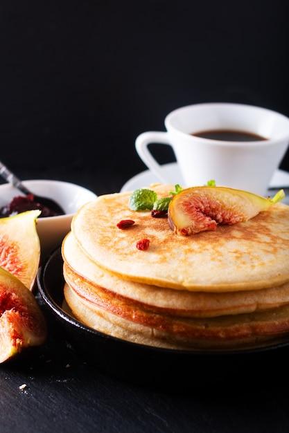 Voedselconcept zelfgemaakte organische pannenkoeken stapel met vijgen ontbijt op zwart Premium Foto