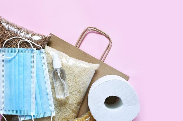 Voedselcrisis op een roze achtergrond. pasta, boekweit, masker, antisepticum, papier. bijdrage. ronduit eten. Premium Foto