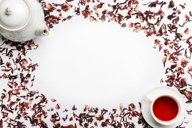 Voedselkader van gietstukken van hibiscusthee, theepot en kop met thee op een witte muur wordt geïsoleerd die Premium Foto