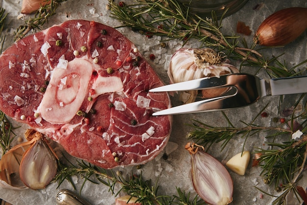 Voedselset, uien, romero, rauw vlees biefstuk, zout, peper, knoflook, olijfolie, vork. close-up, bovenaanzicht Gratis Foto