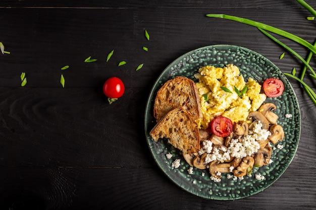 Voedzaam roerei met champignons, ui en tomaten als ontbijt. plaats voor tekst, bovenaanzicht. Premium Foto
