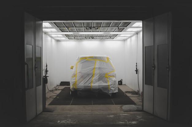 Voertuig bedekt met een wit vel en gele tape in een garage voor autoservice Gratis Foto