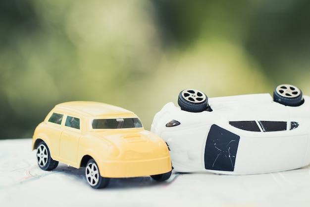 Voertuig verzekering auto-ongeluk concept: twee miniatuur auto's ongevallen crash op weg, gebroken speelgoed Premium Foto