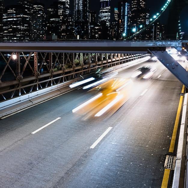Voertuigen op brug met motion blur 's nachts Gratis Foto