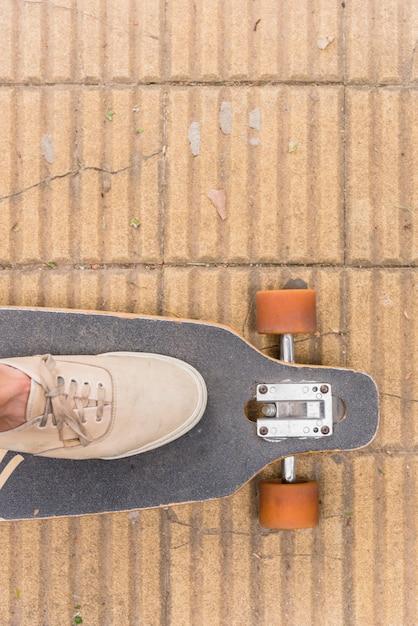 Voet in sneakers staan op longboard Gratis Foto