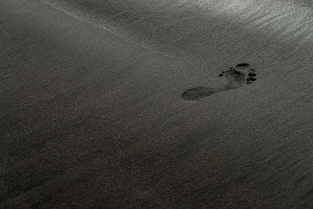 Voetafdruk op een zwarte macrofotografie van het zandstrand. menselijk spoor op een zijdeachtige zwarte strand textuur met ondiepe scherptediepte. minimalistische zwarte achtergrond. voulcanic zandkust van tenerife. Gratis Foto
