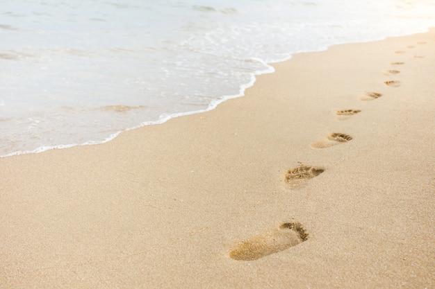 Voetafdruk op zand op de strandachtergrond Premium Foto