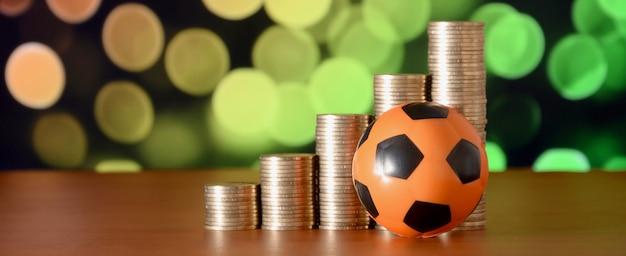 Voetbal en stapels gouden munten Premium Foto