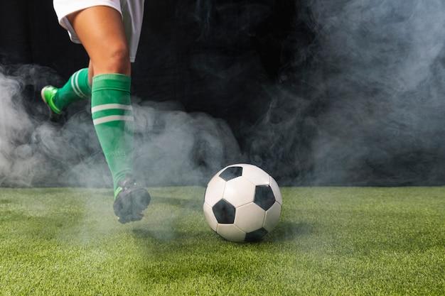 Voetbal in sportkleding spelen met de bal Premium Foto