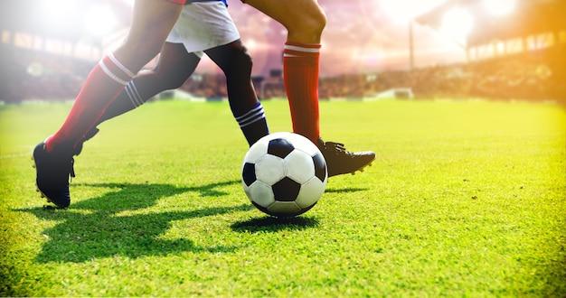 Voetbal of voetbal speler permanent met bal op het veld voor kick voetbal Premium Foto