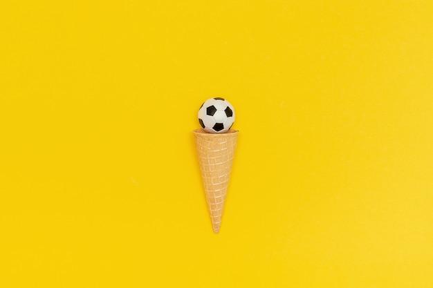 Voetbal of voetbalbal in roomijskegel op gele achtergrond. Premium Foto