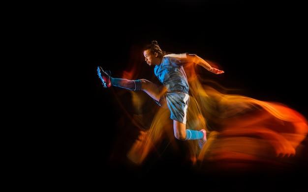 Voetbal of voetballer op zwarte studio Gratis Foto