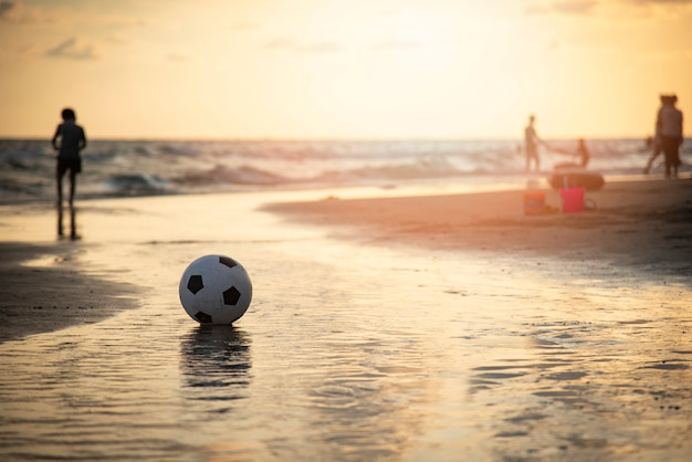 Voetbalbal op zand / speelvoetbal bij het overzees van de strandzonsondergang Premium Foto