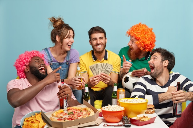Voetbalfans, geluk en leuk concept. dolblij vriend blij dat ze succes hebben op voetbalweddenschappen, een forfaitaire som geld winnen, dollars vasthouden, een lekkere snack eten, rond de tafel zitten, luid lachen, geïsoleerd op blauw Gratis Foto