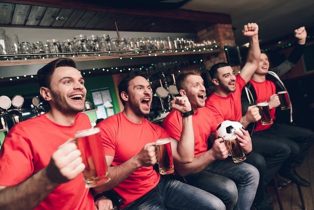 Voetbalfans vieren en juichen het drinken van bier Premium Foto