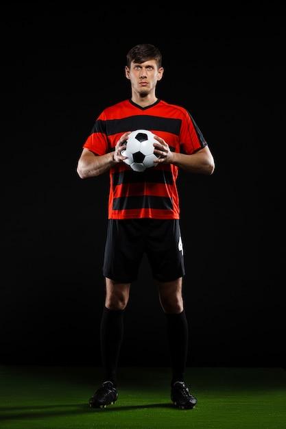 Voetballer die bij groen gebied met bal staart Gratis Foto