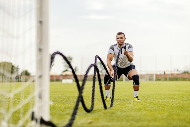Voetballer die oefeningen op het veld doet. hij doet oefeningen met gevechtstouwen. Premium Foto