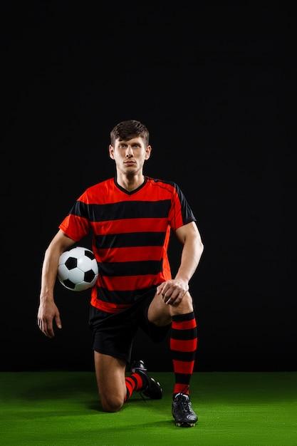 Voetballer met bal staande op de knie, voetballen Gratis Foto