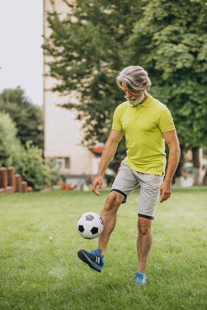 Voetballer van middelbare leeftijd met voetbalbal Gratis Foto