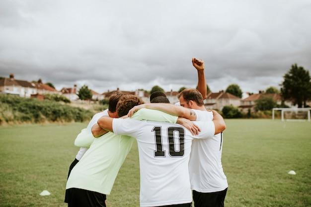 Voetballers die voor een gelijke huddling Premium Foto