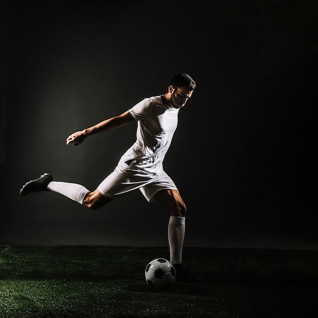 Voetbalspeler schietbal Gratis Foto