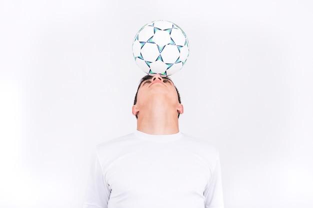 Voetbalster in evenwicht brengende bal op hoofd Gratis Foto