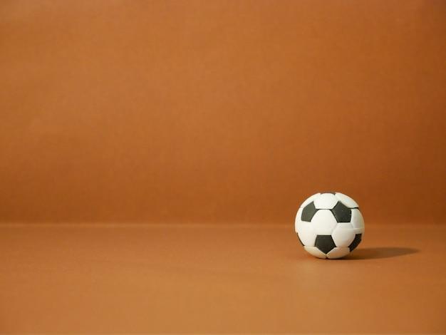 Voetbalvoetbal met exemplaarruimte op bruine achtergrond. Premium Foto