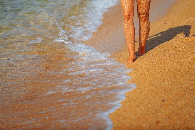 Voeten meisje op het strand. golven die naar de kust lopen Premium Foto