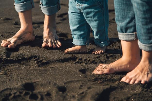 Voeten ouders en baby die zich op zandig strand bevinden Gratis Foto