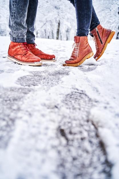 Voeten van een paar op een besneeuwde stoep in bruine laarzen Premium Foto
